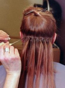 Red-head-woman-having-hair-extensions-sewn-in.