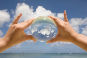 hands-holding-glass-ball-magnifying-the-sky